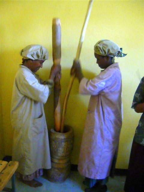Two women process berbere with a mukacha